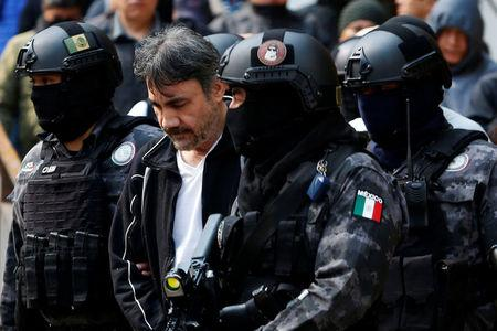 "Accused drug kingpin Damaso Lopez (C), nicknamed ""The Graduate"", is escorted by police officers after he was arrested, in Mexico City, Mexico May 2, 2017. REUTERS/Carlos Jasso"