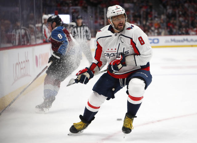 Washington Capitals left wing Alex Ovechkin, front, fights for control of the puck with Colorado Avalanche defenseman Cale Makar in the first period of an NHL hockey game Thursday, Feb. 13, 2020, in Denver. (AP Photo/David Zalubowski)