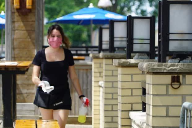 A masked waitress moves among the tables on an outdoor restaurant patio in London, Ont. Women with jobs in the food industry have been particularly hard hit during this pandemic.