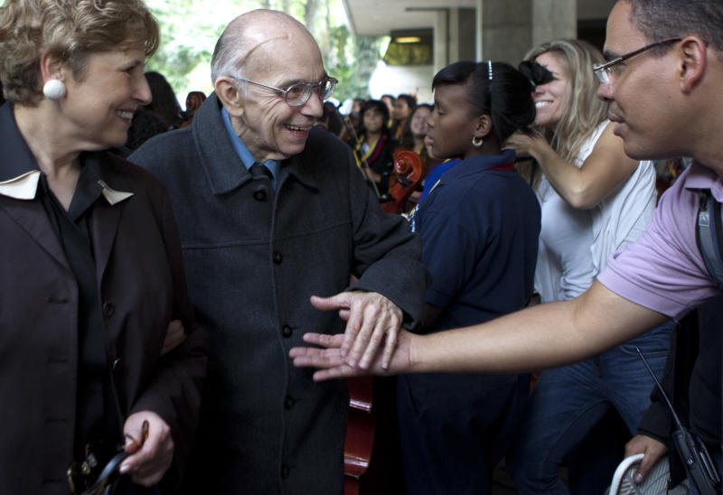 In this Thursday Feb. 16, 2012 photo, President and Chief Executive Officer of the Los Angeles Philharmonic Deborah Borda, left, walks with Jose Antonio Abreu, founder of the National System of Youth and Children's Orchestras of Venezuela, known as El Sistema, as he shakes hands with a fan during an event at Teresa Carreno theater in Caracas, Venezuela. Abreu has revolutionized music education through El Sistema that has become a model worldwide and has produced talents such as star conductor Gustavo Dudamel. (AP Photo/Ariana Cubillos)