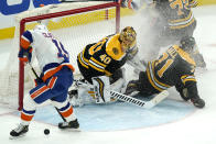 New York Islanders right wing Cal Clutterbuck, left, can't control the puck to get a shot off as Boston Bruins goaltender Tuukka Rask, center, and Bruins left wing Taylor Hall, right, protect the goal after a flurry in the first period of an NHL hockey game, Monday, May 10, 2021, in Boston. (AP Photo/Elise Amendola)