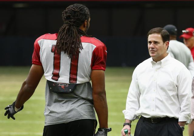 Arizona Cardinals wide receiver Larry Fitzgerald talks with Arizona Gov. Doug Ducey during training camp in 2017. (AP Photo/Ross D. Franklin)