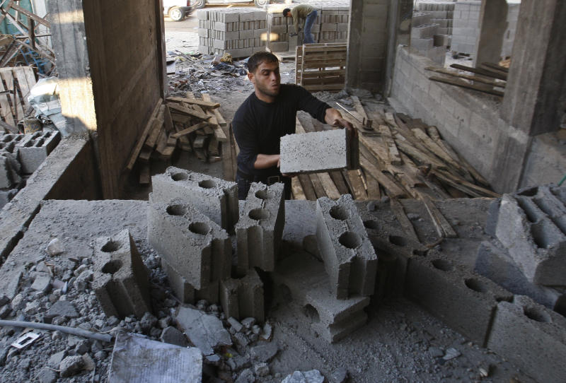 """Palestinian workers rebuild a house in Gaza City, Monday, Dec. 31, 2012. Israel has started allowing long-banned building materials into the Gaza Strip, its first key concession to the territory's Hamas rulers under a cease-fire that ended eight days of intense fighting last month, the military said Monday. A Hamas official described the quantity sent so far as """"cosmetic"""" and Gaza economists said it would take years of round-the-clock shipments to even make a dent in the gap left by the five years of blockade. (AP Photo/Hatem Moussa)"""