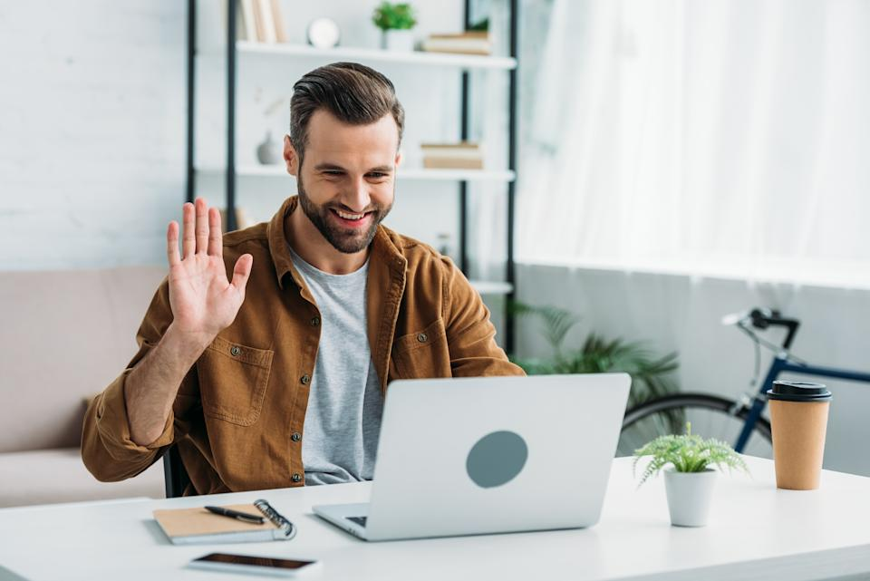 handsome and happy man smiling and looking at screen of laptop