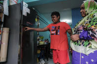 Habib Sulthan smiles next to his mother, Sukkuriya Beevi, a 51-year old cleaner from India, as they look at a refrigerator donated by Keeping Hope Alive on Sunday, Oct. 4, 2020 in Singapore. Members of the volunteer group conduct weekend door-to-door visits to deliver goods or provide services to people in need. (AP Photo/Ee Ming Toh)
