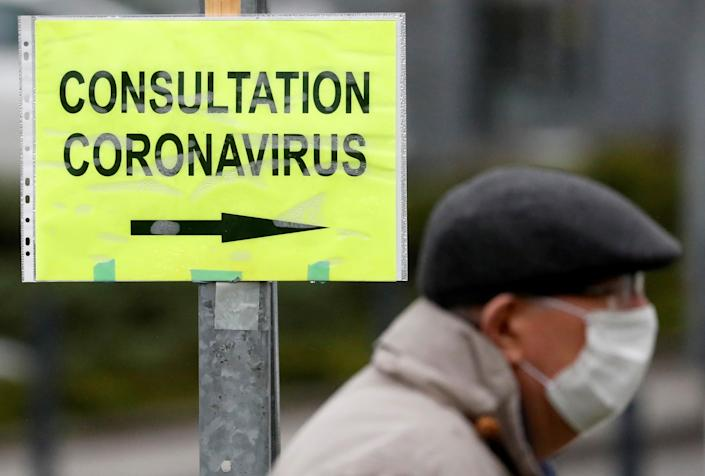 A man wears a protective mask as he walks in front of a placard indicating coronavirus disease (COVID-19) consultations at an entrance of the hospital in Vannes, France March 10, 2020. (Stephane Mahe/Reuters)