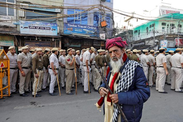 A Muslim man looks on as police officers conduct a flag march in a street outside Jama Masjid, before Supreme Court's verdict on a disputed religious site claimed by both majority Hindus and Muslim in Ayodhya, in the old quarters of Delhi, India, November 9, 2019. REUTERS/Adnan Abidi TPX IMAGES OF THE DAY