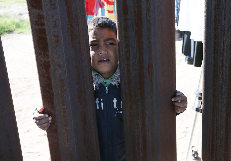 A young boy peers through the border fence from the Anapra area of Juarez Saturday, Nov. 3.