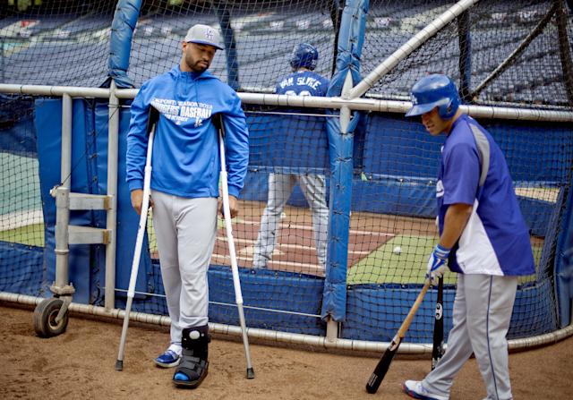 Los Angeles Dodgers' Matt Kemp, left, stands on crutches as teammate Jerry Hairston Jr. gets ready to hit during baseball batting practice, Wednesday, Oct. 2, 2013, in Atlanta. The Dodgers play the Atlanta Braves in Game 1 of the NL division series in Atlanta on Thursday. Kemp is out of the playoffs with complications from a sprained left ankle. (AP Photo/David Goldman)