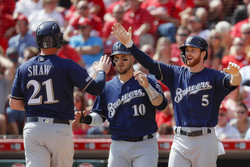 From left, Milwaukee Brewers' Travis Shaw, Yasmani Grandal, and Cory Spangenberg celebrate after scoring on a three-run double hit by Orlando Arcia, off Cincinnati Reds starting pitcher Luis Castillo, in the fourth inning of a baseball game, Thursday, Sept. 26, 2019, in Cincinnati. (AP Photo/John Minchillo)