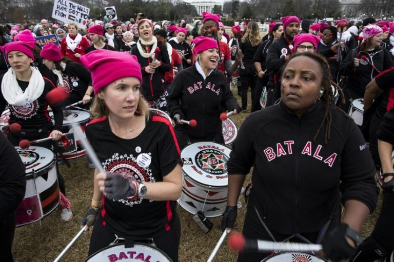 """Roused by fiery speeches and led by women in pink """"pussyhats,"""" hundreds of thousands flooded Washington and cities across the US to protest President Donald Trump"""