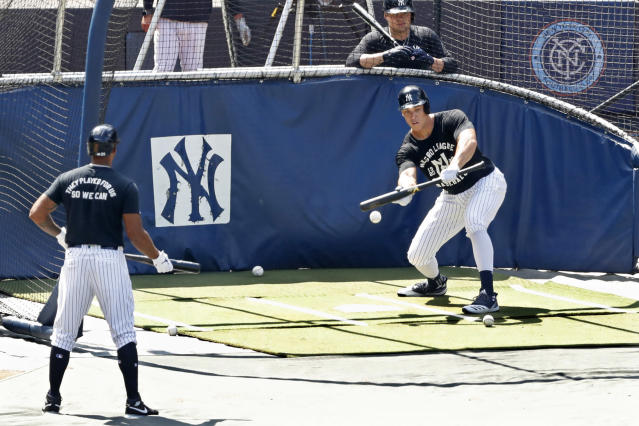 New York Yankees Aaron Hicks, left, and Luke Voit, above right, watch as Aaron Judge begins his batting practice with a bunt at Yankees summer baseball training camp, Wednesday, July 15, 2020, at Yankee Stadium in New York. (AP Photo/Kathy Willens)