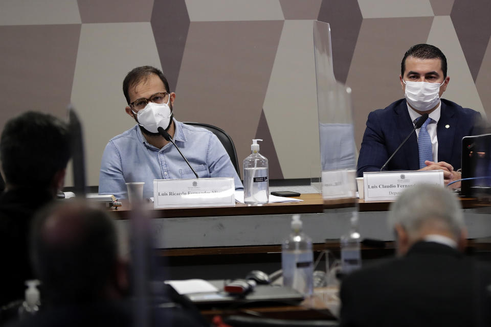 Luis Ricardo Fernandes Miranda, head of imports of the Ministry of Health, left, and his brother, Deputy Luis Miranda, attend a hearing before the Senate for an investigation into the government's management of the COVID-19 pandemic, in Brasilia, Brazil, Friday, June 25, 2021. (AP Photo/Eraldo Peres)