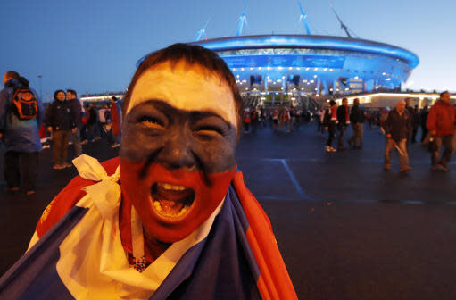 A Russian fan celebrates Russia's 3-1 victory over Egypt in the group A match at the 2018 soccer World Cup near the St. Petersburg stadium in St. Petersburg, Russia, Tuesday, June 19, 2018. (AP Photo/Dmitri Lovetsky)