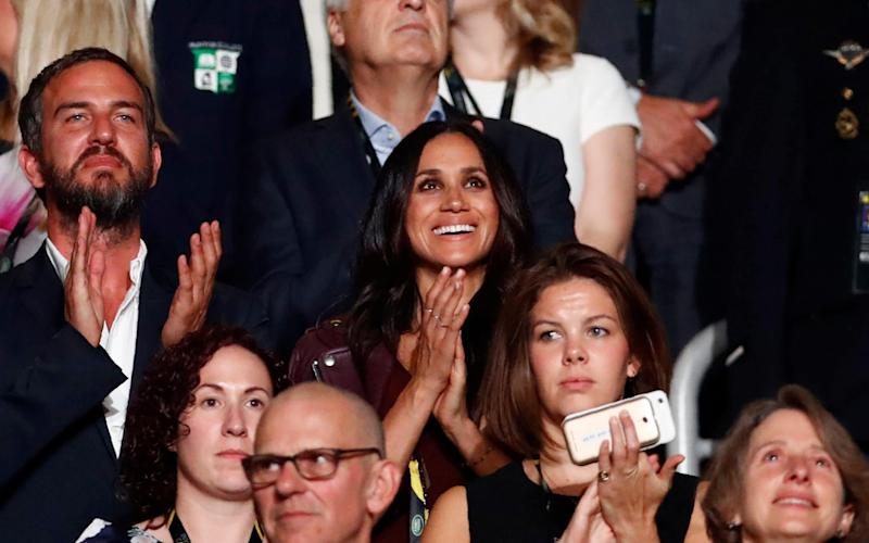 Meghan Markle (center, wearing dark red), girlfriend of Britain's Prince Harry, applauds during the opening ceremony for the Invictus Games in Toronto - REUTERS