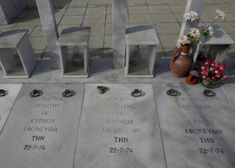 """Flowers left by relatives adorn the grave of a person killed during the 1974 Turkish invasion of Cyprus, while on the left are seen two graves reading """"unknown civilian"""" in Greek, Lakatamia military cemetery in the Cypriot capital Nicosia, on Thursday, Nov. 29, 2012. A Cyprus court has ordered the government to pay Euro 324,000 ($419,668 approx) in damages to the wife and two daughters of a soldier who was killed during Turkey's 1974 invasion of the country but who was listed as missing in action for more than two decades. (AP Photo / Petros Karadjias)"""