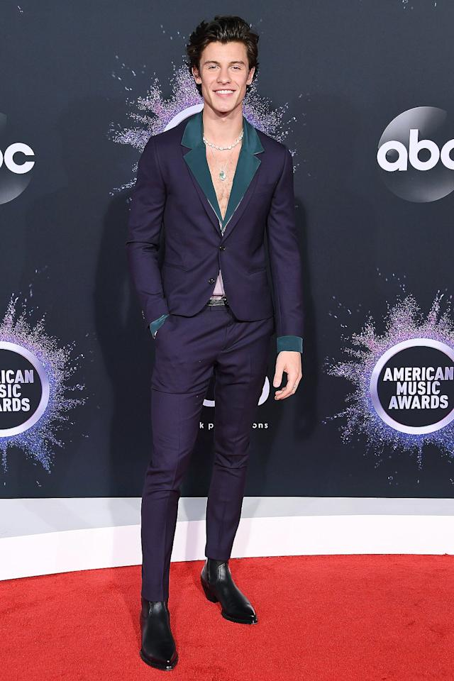wears a plunging dark purple Paul Smith suit featuring teal lapels, teamed with a diamond necklace and an emerald green pendent.