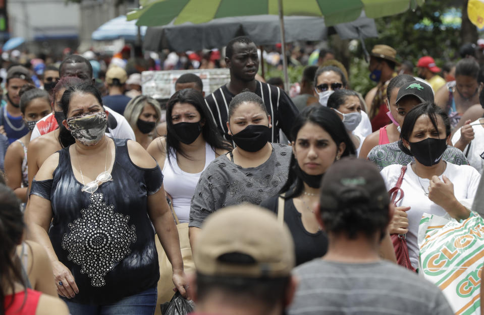 Pedestrians cross a street in a crowded downtown shopping district in Sao Paulo, Brazil, Tuesday, Dec. 15, 2020, amid the new coronavirus pandemic. (AP Photo/Andre Penner)