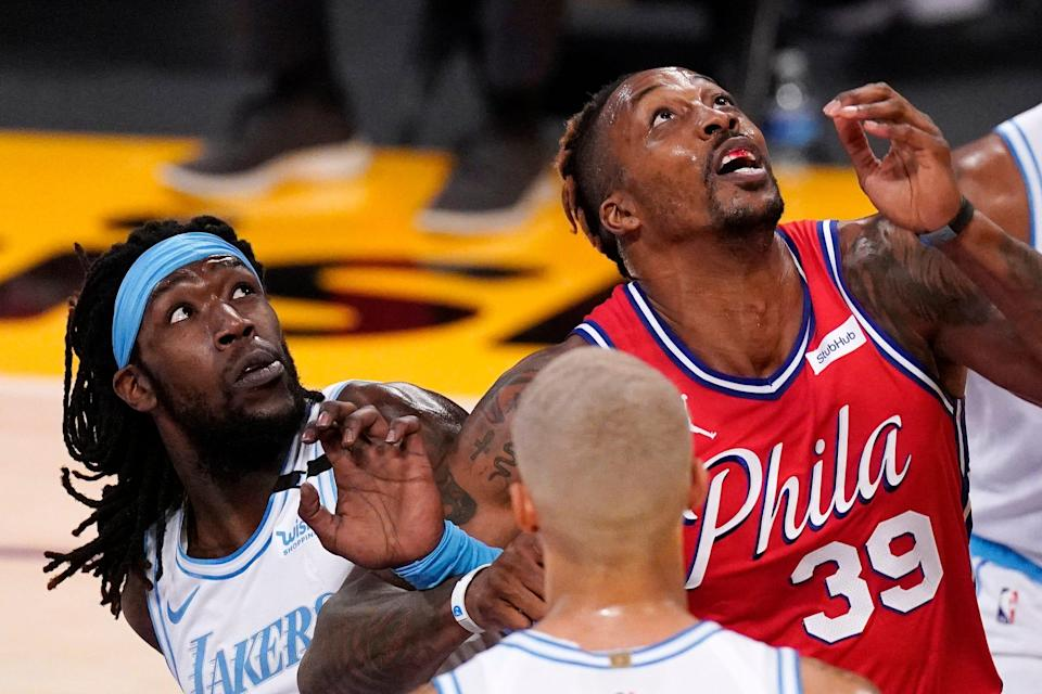 Los Angeles Lakers center Montrezl Harrell, left, and Philadelphia 76ers center Dwight Howard battle for a rebound during the first half of an NBA basketball game Thursday, March 25, 2021, in Los Angeles. (AP Photo/Mark J. Terrill)