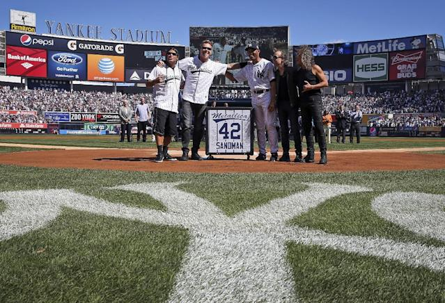 "New York Yankees relief pitcher Mariano Rivera, third from right, is joined by the members of the heavy metal band Metallica, from left, Robert Trujillo, James Hetfield, Lars Ulrich and Kirk Hammett as Riverea is honored in a pregame ceremony at Yankees Stadium before the Yankees baseball game against the San Francisco Giants, Sunday, Sept. 22, 2013, in New York. The 13-time All-Star closer is retiring at the end of this season. Rivera's signature song when he comes into the game is 'Enter Sandman"" by the band. (AP Photo/John Minchillo)"