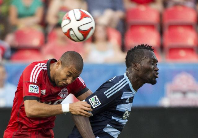Toronto FC defender Justin Morrow, left, heads the ball past Sporting Kansas City C.J. Sapong during the first half of an MLS soccer game Saturday, July 26, 2014, in Toronto. (AP Photo/The Canadian Press, Nathan Denette)