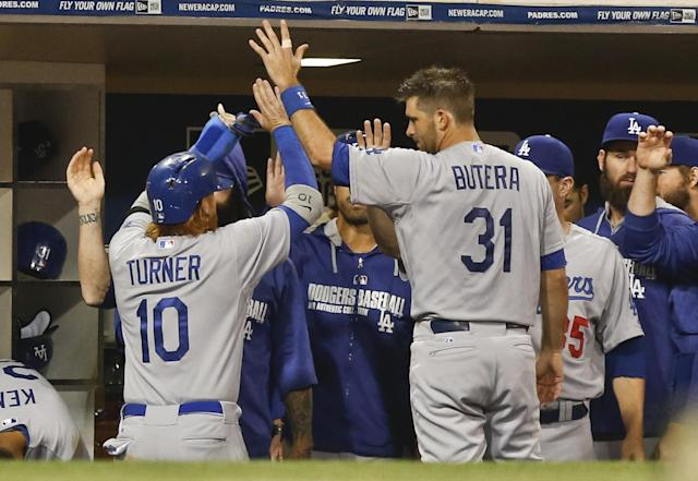 Los Angeles Dodgers' Justin Turner is greeted at the dugout after scoring against the San Diego Padres on a hit by Hanley Ramirez during the fifth inning of a baseball game Saturday, June 21, 2014, in San Diego. (AP Photo/Lenny Ignelzi)