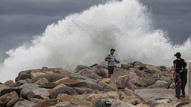 PHOTO: A tourist poses for a photo in front breaking waves before the expected arrival of Hurricane Lorena, in Los Cabos, Mexico, Friday, Sept. 20, 2019. (Fernando Castillo/AP)
