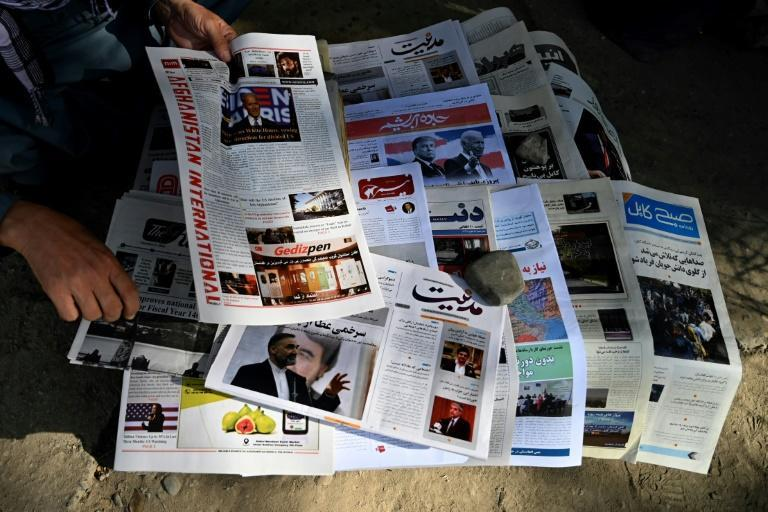 A vendor arranges newspapers declaring Joe Biden's victory at a kiosk in the Afghan capital, Kabul
