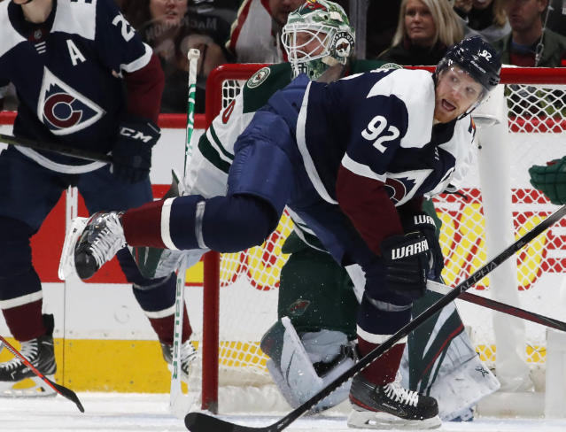 Colorado Avalanche left wing Gabriel Landeskog, front, struggles to stay on his skates as he looks for a pass while in front of Minnesota Wild goaltender Devan Dubnyk in the second period of an NHL hockey game Friday, Dec. 27, 2019, in Denver. (AP Photo/David Zalubowski)