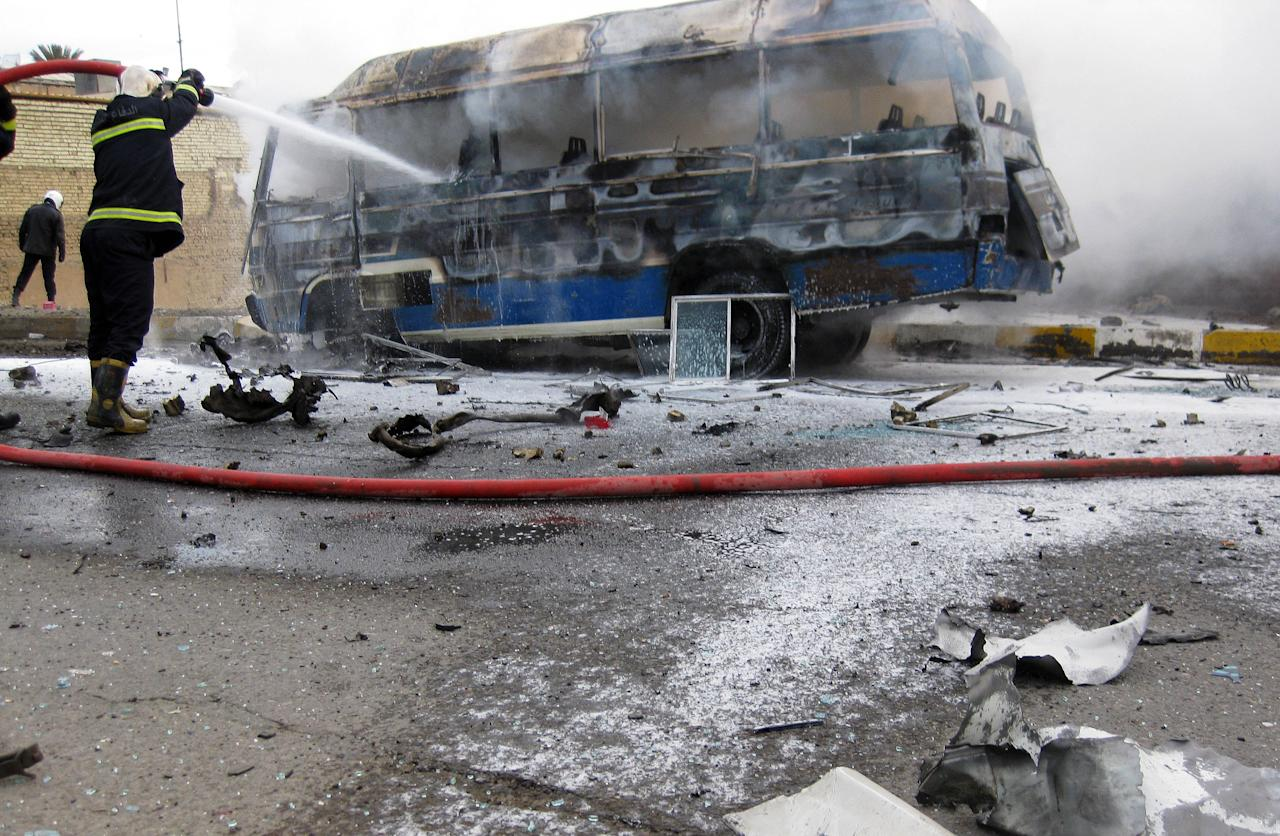 Iraqi firefighters try to extinguish a burning bus at the scene of a car bomb explosion in Baghdad, Iraq, Thursday, Feb. 23, 2012. Iraqi officials say a string of morning attacks across Baghdad has killed and injured dozens of Iraqis. (AP Photo/Hadi Mizban)