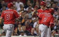 Los Angeles' Mike Trout, center, congratulates Kendrys Morales (8) and Erick Aybar (2) after scoring on a single by Chris Iannetta in the third inning of a baseball game against the Boston Red Sox at Fenway Park in Boston, Thursday, Aug. 23, 2012. (AP Photo/Charles Krupa)