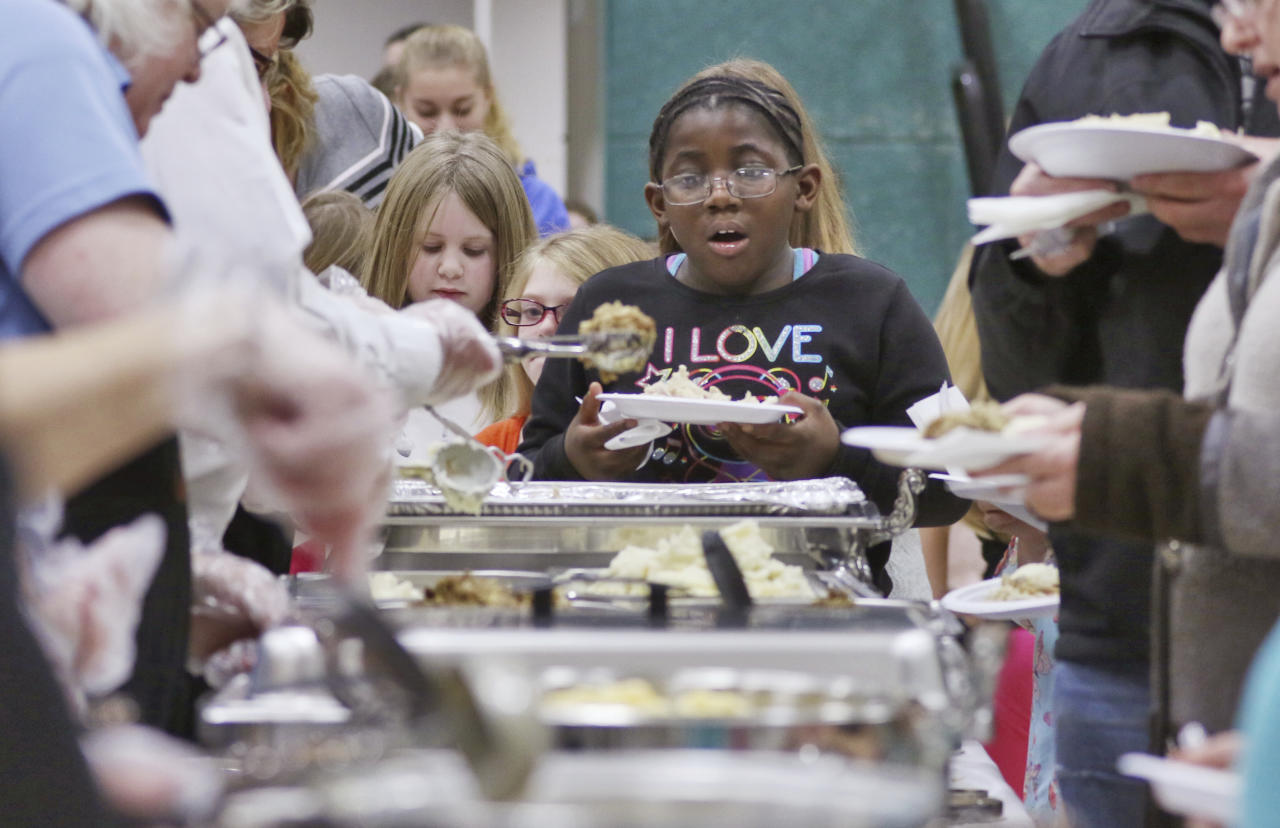 The mouth of Elijaah Webster, 7, of Milwaukee, drops as she sees the amount of food being served during the annual Thanksgiving dinner at the Boys and Girls Club of Washington County on Tuesday, Nov. 21, 2017 in West Bend, Wis. Volunteers with First Weber and the Boys and Girls Club of Washington County helped serve dinner to nearly 300 children across the Jackson, Kewaskum, Hartford and West Bend. (John Ehlke/West Bend Daily News via AP