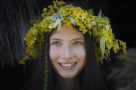 """A girl wearing a crown made of flowers takes part in an event inspired by pre-Christian traditions at the Dimitrie Gusti Village Museum in Bucharest, Romania, Thursday, June 24, 2021. According to pre-Christian traditions, fairies, called in Romanian """"Sanziene,"""" come to earth around the summer solstice bringing fertility to land and beings for the coming summer. (AP Photo/Vadim Ghirda)"""