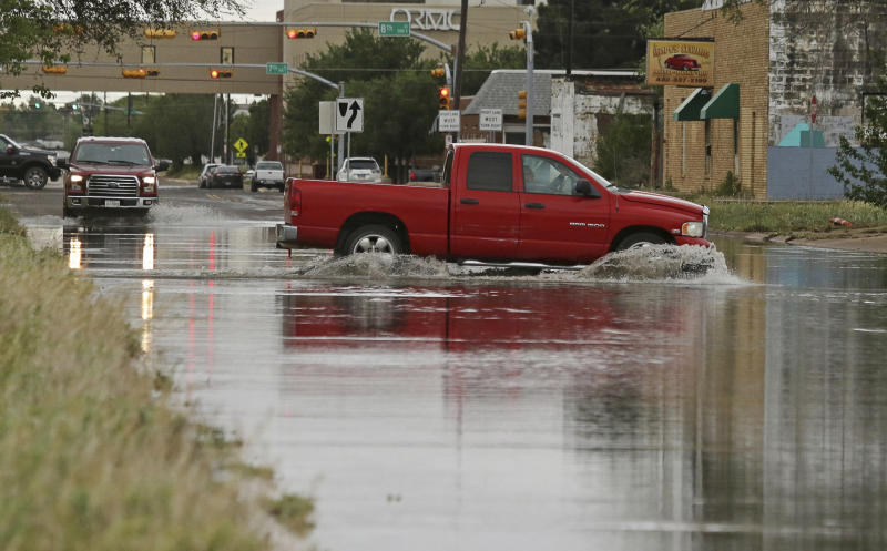 A vehicle drives through a flooded section of Muskingum Avenue on Saturday April,13 2019 in Odessa Texas