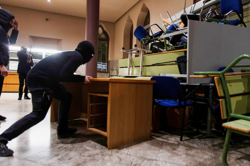 A demonstrator in support of rap singer Pablo Hasel uses a table to set up a barricade against a door of the rectory of Lleida University