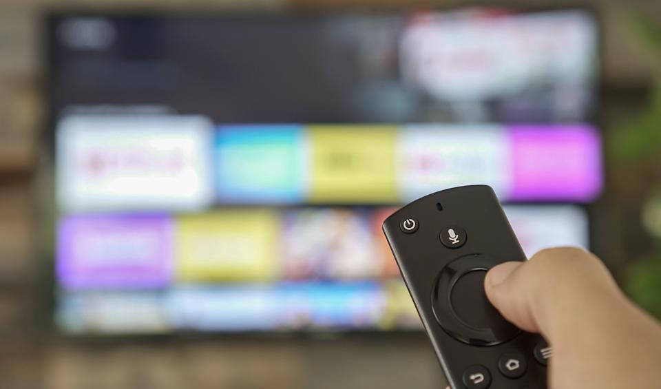Male hand holding the TV remote control and changing TV channels. Channel surfing, focused on the hand and remote control. Internet TV.