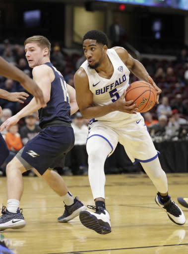 Buffalo's CJ Massinburg (5) drives past Akron's Scott Walter (14) during the first half of an NCAA college basketball game of the Mid-American Conference tournament, Thursday, March 14, 2019, in Cleveland. (AP Photo/Tony Dejak)