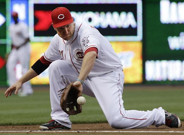 Cincinnati Reds third baseman Todd Frazier fields a ground ball hit by Pittsburgh Pirates' Starling Marte in the first inning of a baseball game, Monday, June 17, 2013, in Cincinnati. Frazier threw Marte out at first. (AP Photo/Al Behrman)