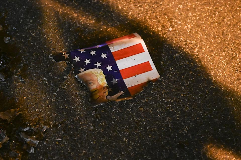 A poster showing the US flag and the face of US President Donald Trump is seen burnt on the street after anti-Trump demonstrators set it on fire in Black Lives Matter Plaza in Washington, DC on November 14, 2020. (Photo by Roberto SCHMIDT / AFP) (Photo by ROBERTO SCHMIDT/AFP via Getty Images)