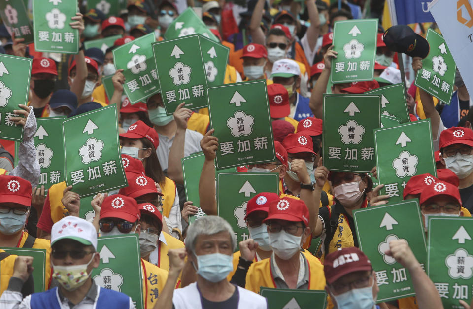 "Taiwanese workers hold slogans reading ""Increase Salary"" during a May Day rally in Taipei, Taiwan, Saturday, May 1, 2021. Thousands of protesters from different labor groups protest on the street to ask for increasing salary and securing annuity. (AP Photo/Chiang Ying-ying)"