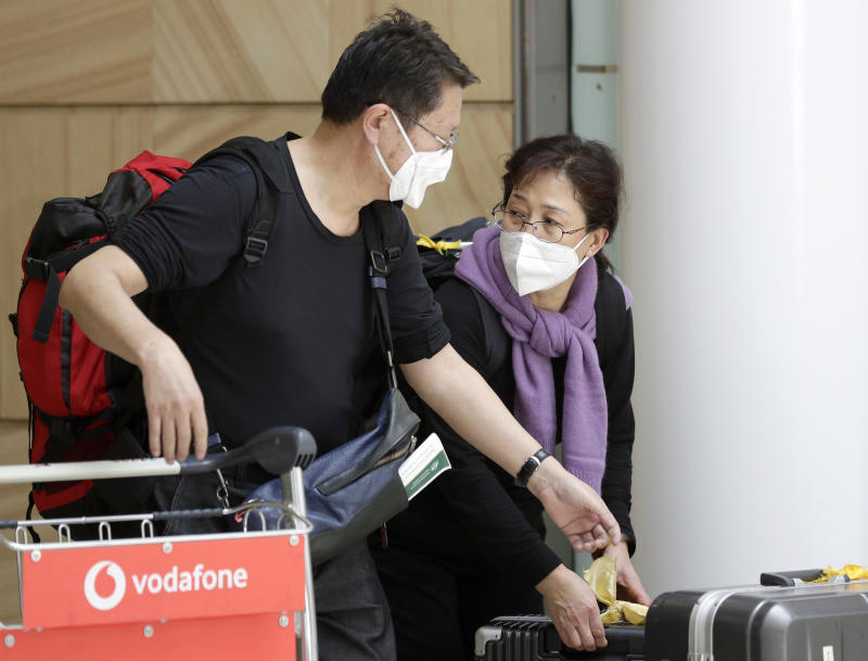 Travelers wearing face masks arrive in Sydney Thursday, Jan. 23, 2020, on a flight from Wuhan, China. China closed off a city of more than 11 million people as part of a radical effort to prevent the spread of a deadly virus that has sickened more than 500 people and has begun to spread to other cities and countries in the region. (AP Photo/Rick Rycroft)