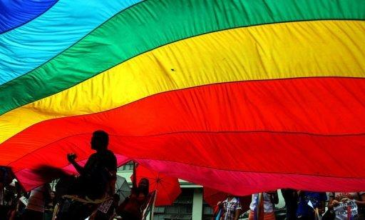 A gay activist is silhouetted by the rainbow flag during a rally of the lesbian, gay, transgender and bisexual community at the University of the Philippines in the town of Los Banos, Laguna province, south of Manila. Gay sex in a conservative Catholic society where the influential church forbids the use of condoms is fuelling an alarming rise of HIV infections in the Philippines, experts warn