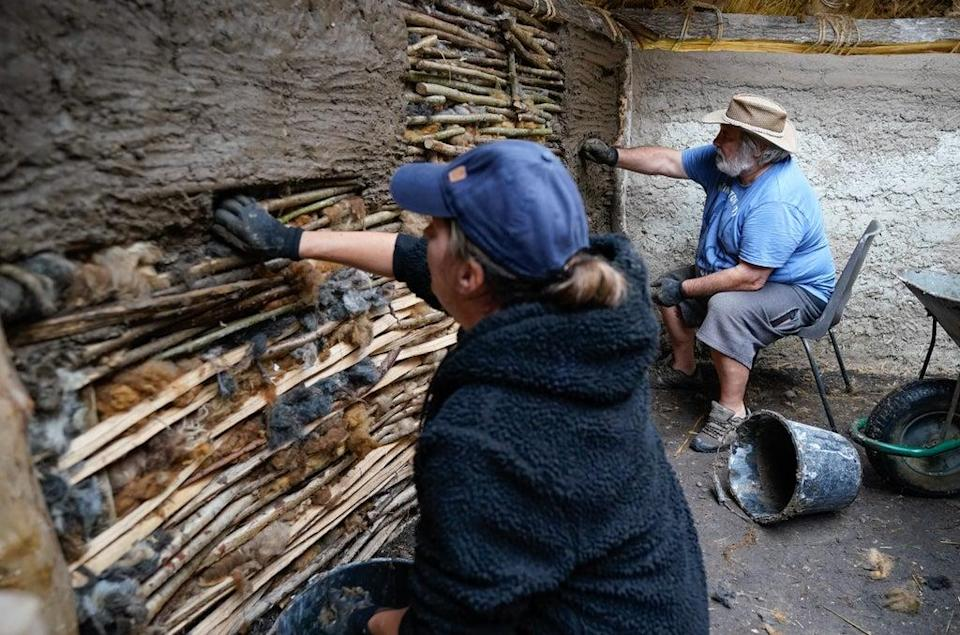 Veterans Kevin Reilly (right) and Jackie Crutchfield apply daub to some wattle in the new Bronze Age roundhouse (Andrew Matthews/PA) (PA Wire)
