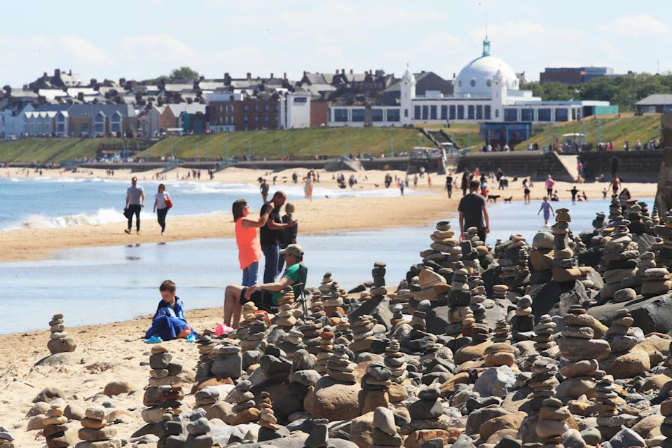 People enjoy the hot weather at Whitley Bay beach in Tyneside as people flock to parks and beaches with lockdown measures eased. (Photo by Owen Humphreys/PA Images via Getty Images)