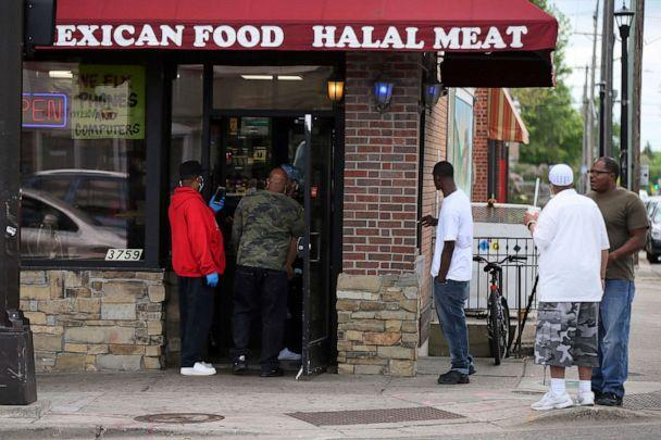 PHOTO: Men gather outside a grocery store Tuesday, May 26, 2020 near where a black man died in police custody Monday night in Minneapolis. (Jim Mone/AP)