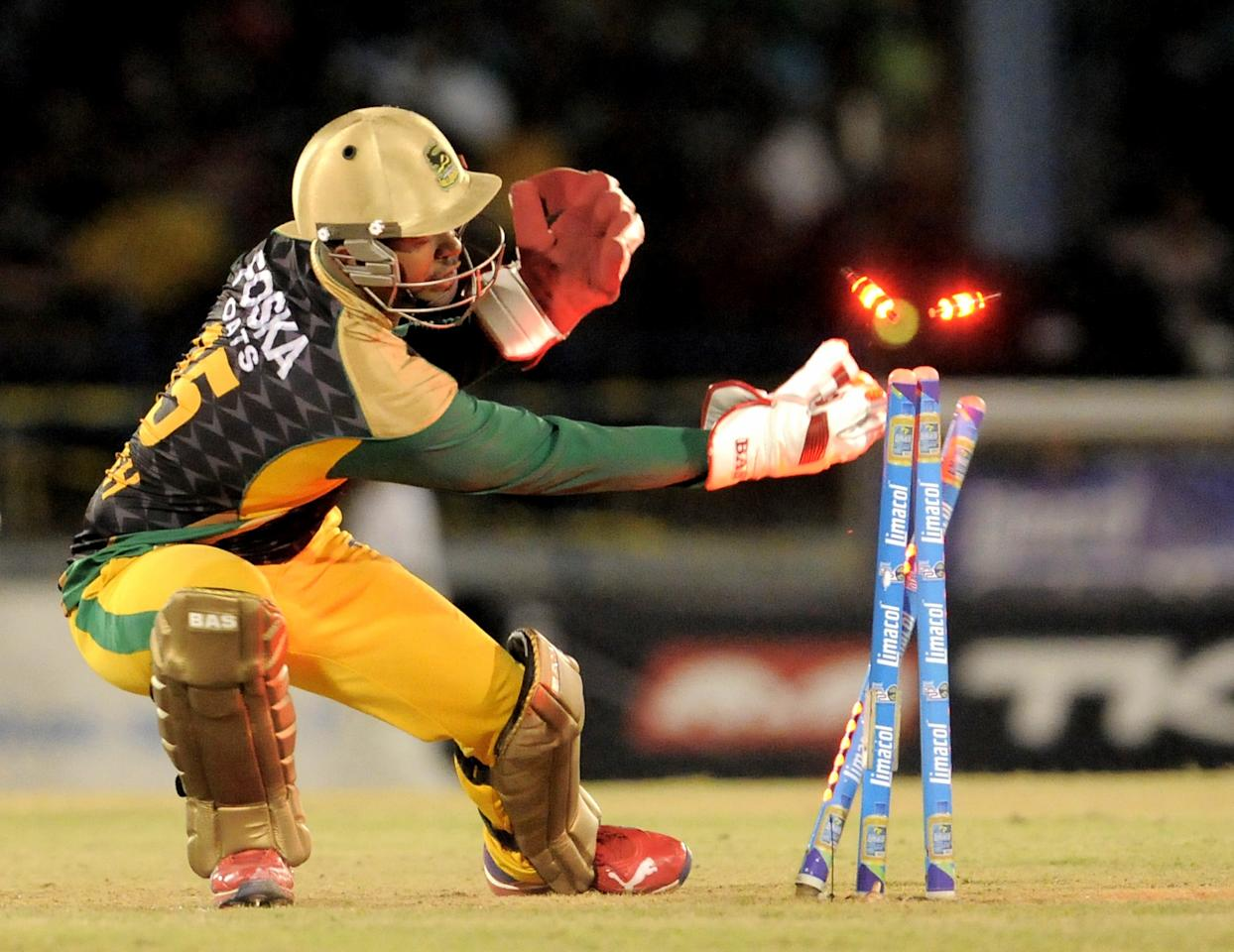 PORT OF SPAIN, TRINIDAD AND TOBAGO - AUGUST 24:  Keeper Carlton Baugh of Jamaica Tallawahs run out Guyana Amazon Warriors Sunil Narine during the Final of the Caribbean Premier League between Guyana Amazon Warriors v Jamaica Tallawahs at Queens Park Oval on August 24, 2013 in Port of Spain, Trinidad and Tobago. (Photo by Randy Brooks/Getty Images Latin America for CPL)