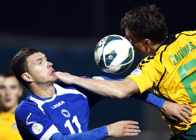 Bosnia's Edin Dzeko, left, is challenged by Lithuania's player Marius Zaliukas during the World Cup group G qualifying soccer match between Lithuania and Bosnia in Kaunas, Lithuania, Tuesday, Oct. 15, 2013. (AP Photo/Mindaugas Kulbis)