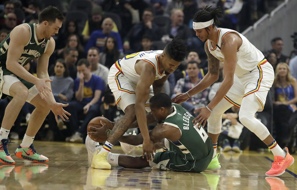 Milwaukee Bucks' Eric Bledsoe (6) passes the ball between the legs of Golden State Warriors' Glenn Robinson III to teammate Pat Connaughton, left, during the first half of an NBA basketball game Wednesday, Jan. 8, 2020, in San Francisco. At right is Warriors' Damion Lee. (AP Photo/Ben Margot)