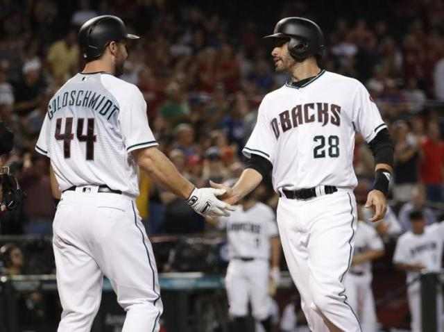 Arizona Diamondbacks' Paul Goldschmidt (44) greets teammate J.D. Martinez (28) after they scored on a base hit by teammate Brandon Drury against the Los Angeles Dodgers during the first inning of a baseball game, Tuesday, Aug. 29, 2017, in Phoenix. (AP Photo/Matt York)