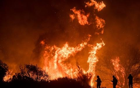 Motorists on Highway 101 watch flames from the Thomas fire leap above the roadway north of Ventura - Credit: AP